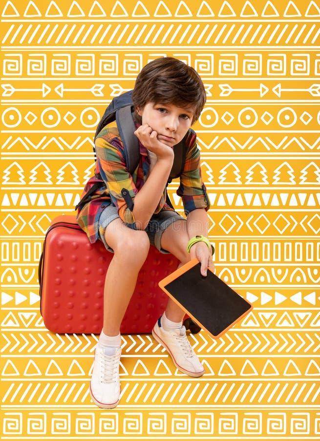 Düsteres Kind, das beim Sitzen auf dem Gepäck ermüdet glaubt stockfotografie