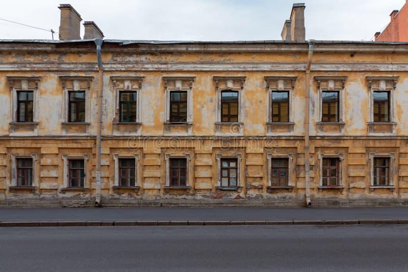 Düsteres zweistöckiges altes Haus mit dunklen Fenstern und eine zerbröckelnde Fassade auf einer verlassenen Straße stockbilder