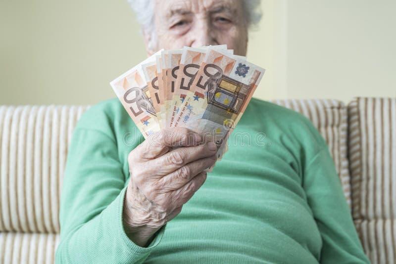 Dłoń osoby starszej posiadającej banknoty euro zdjęcia stock