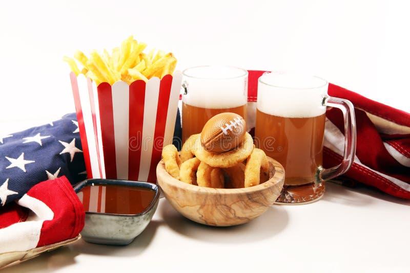 Dłoniaki i cebulkowi pierścionki dla futbolu na stole Wielki dla puchar gry obrazy royalty free