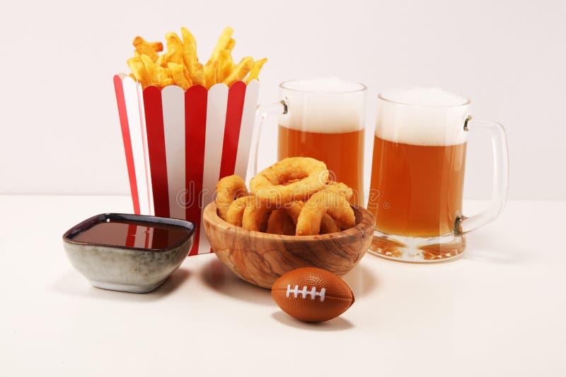 Dłoniaki i cebulkowi pierścionki dla futbolu na stole Wielki dla puchar gry zdjęcia stock