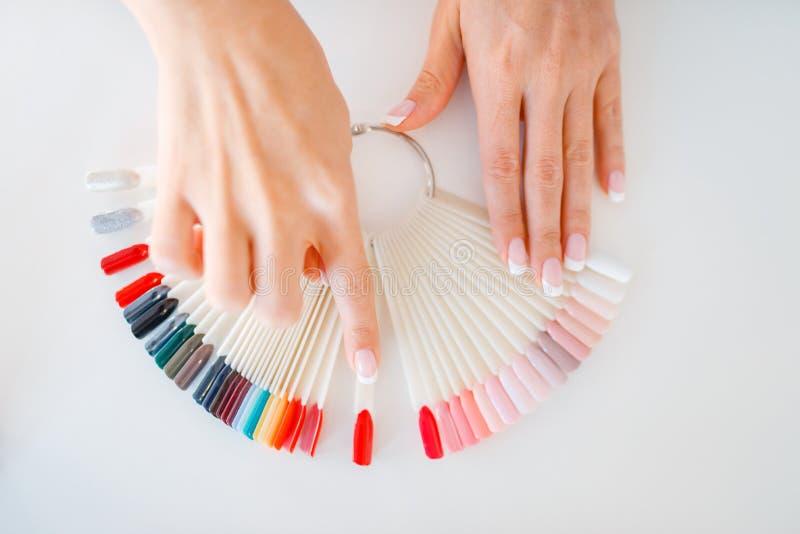 Dłonie i kolorowa paleta lakieru do paznokci zdjęcie royalty free