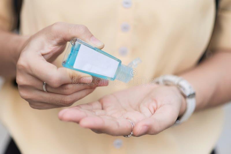 Dłonie kobiety stosujące dozownik żelu do czyszczenia rąk, przeciwko nowemu koronawirusowi lub chorobie wirusa Corona Covid- 19 w zdjęcia royalty free