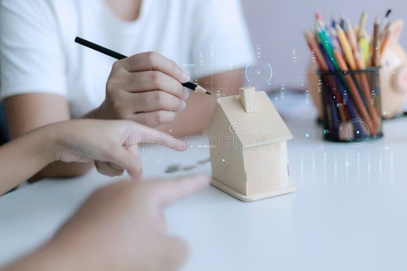 Dłonie matki i córki ojca rodziny wskazujące na drewniany model domu metafory marzenia o budowaniu domu i dekoracji lub fotografia royalty free