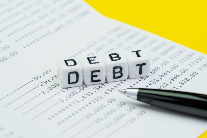 Dług, pieniężny zobowiązanie lub pieniądze zarządzania pojęcie, mały biały sześcian blokujemy z abecadłem buduje słowo dług na ba zdjęcia stock