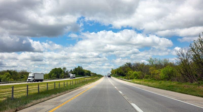Długa autostrada w amerykańskiej wsi, błękitny chmurnego nieba tło obrazy stock
