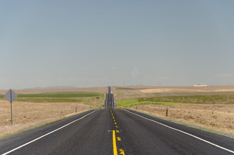 Długa droga w odległość z rolną ziemią obraz stock