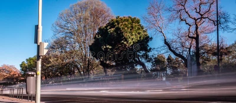 Długa fotografia nabierająca ujawnienia Lisbon aleja z Pięknym greenery i niebieskim niebem z szybkimi poruszającymi samochod fotografia stock