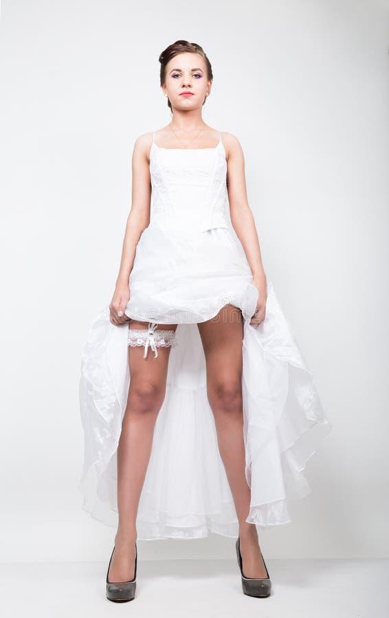 Długa panna młoda w ślubnej sukni podnoszących oblamowanie jej suknia bridal uczesaniu i, prowokaci figlarnie panna młoda obrazy royalty free