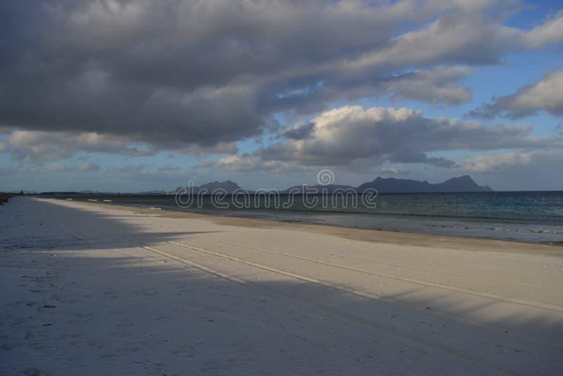 Długa piasek plaża z górami w tle obraz royalty free