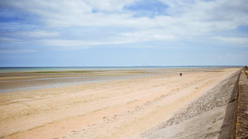 Długa spokój plaża z błękitnym chmurnym niebem normandy obraz royalty free