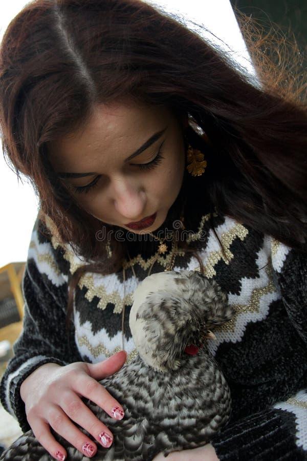Długa z włosami dziewczyna na gospodarstwie rolnym całuje puszystego kurczaka obraz stock