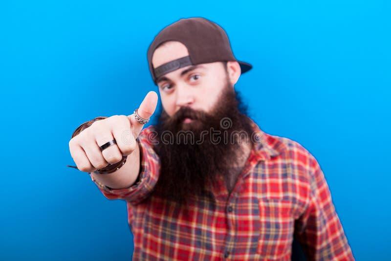 Długi brodaty mężczyzna pokazuje kciuki do kamery i brzęczeń tylko obrazy stock