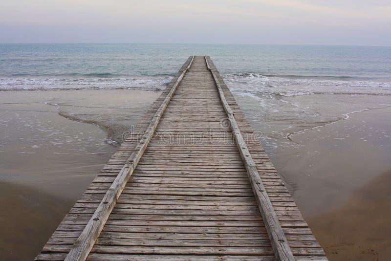Długi drewniany boardwalk na plaży obraz royalty free