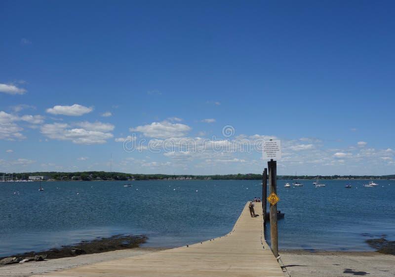 Długi drewniany nabrzeże z ludźmi podpisuje, łodzie, chmury Casco zatoka, Portlandzki Maine Czerwiec 2018 zdjęcie stock