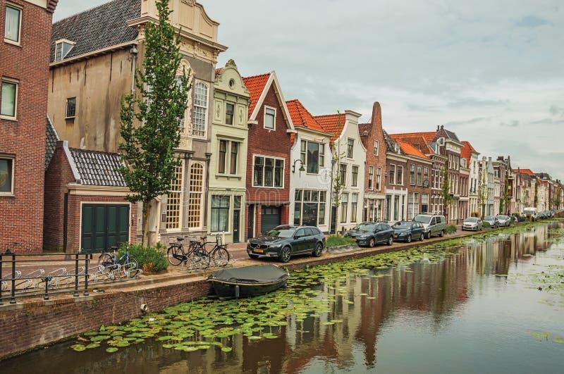 Długi kanał z nadwodnymi roślinami, cegła domami na swój banku i chmurnym dniem przy Gouda, zdjęcie stock