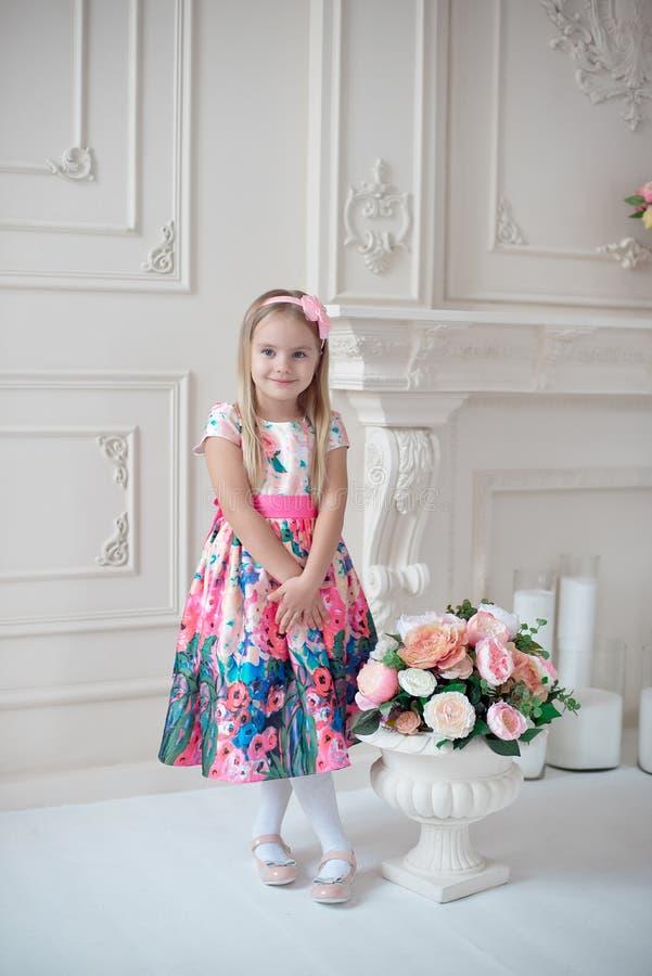 Długi mały uśmiechnięty dziewczyny dziecko w kolorowy sukni pozować salowy zdjęcie stock