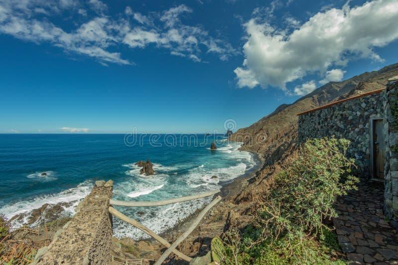 Długi naturalny plażowy Benijo Lawy skała w wodzie Błękitny denny horyzont, naturalny niebieskie niebo i puszysty biały chmury tł fotografia stock