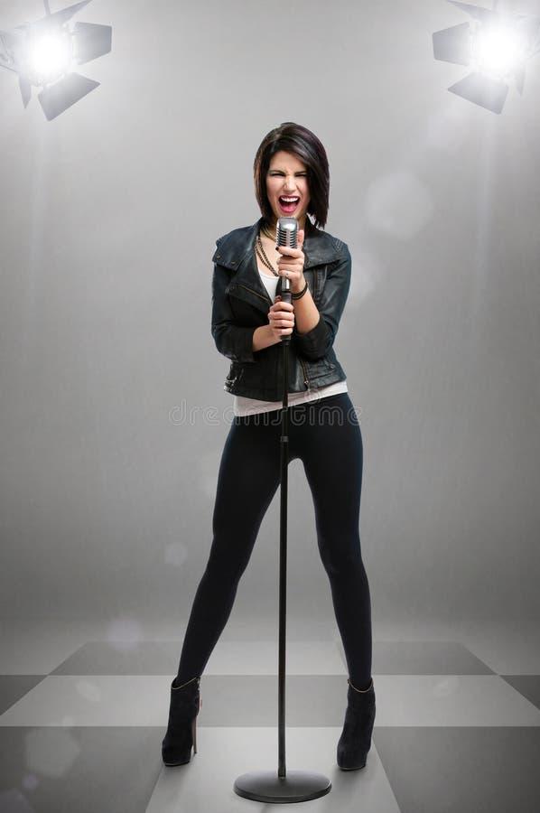 Długi portret rockowy piosenkarz z mic pod projektorami zdjęcia stock