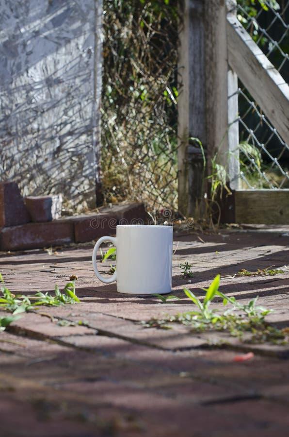 Długi solo pusty biały kawowy kubek przed ogródem zdjęcia royalty free