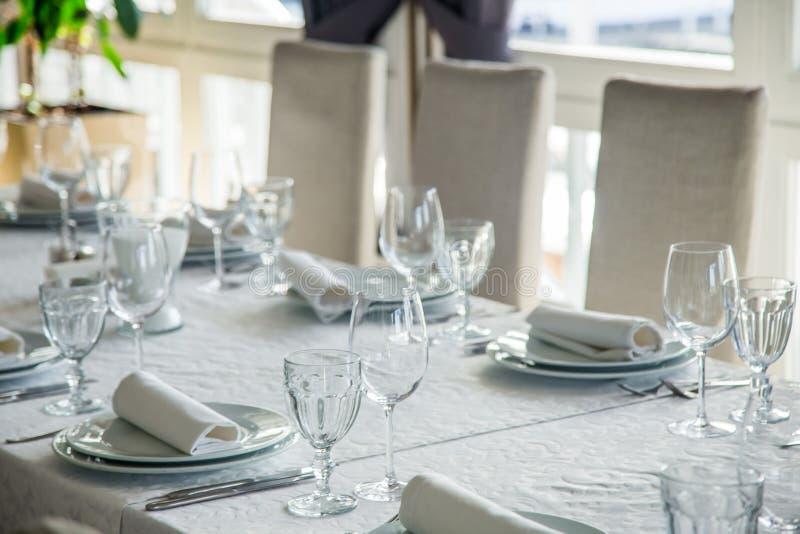 Długi stół zakrywający z białym tablecloth z cutlery i szkłami obraz stock