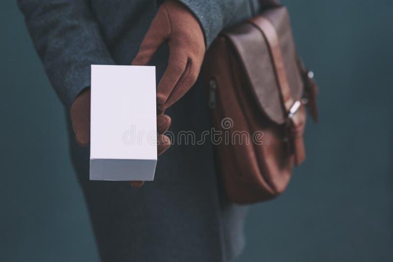 Długi sztandar z egzaminem próbnym w górę białego pudełka od smartphone Dziewczyna w żakiecie i brąz rękawiczkach trzyma prezent  fotografia royalty free