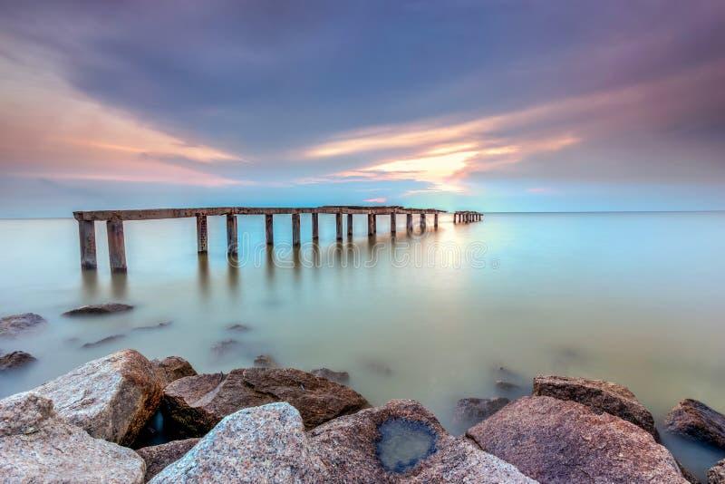 Długi ujawnienie obrazek zaniechany stary jetty z chmurnym przedtem fotografia stock