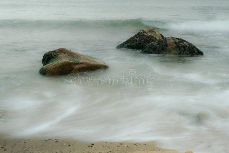 Długi ujawnienie ocean fale, płynie wokoło gałęzatki zakrywał głazy, Blokowa wyspa, RI zdjęcie stock