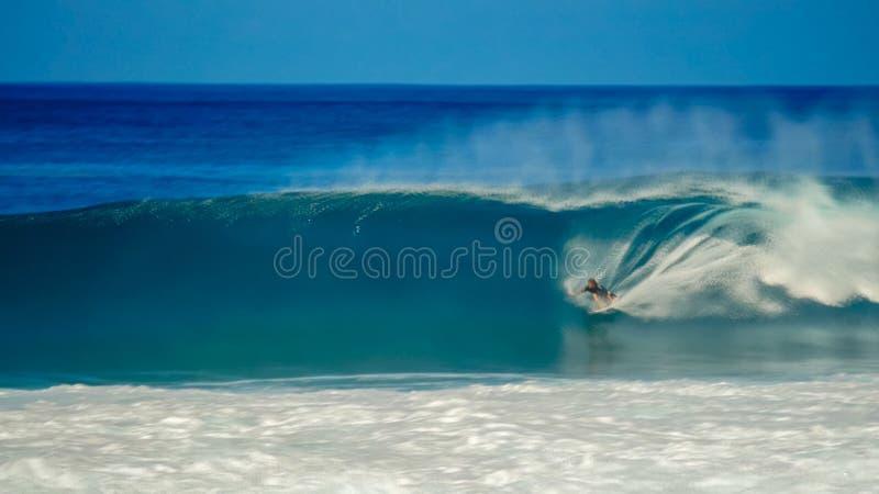 Długi ujawnienie strzał surfingowiec dostaje tubki przejażdżkę przy tylnymi drzwiami rurociąg zdjęcia stock
