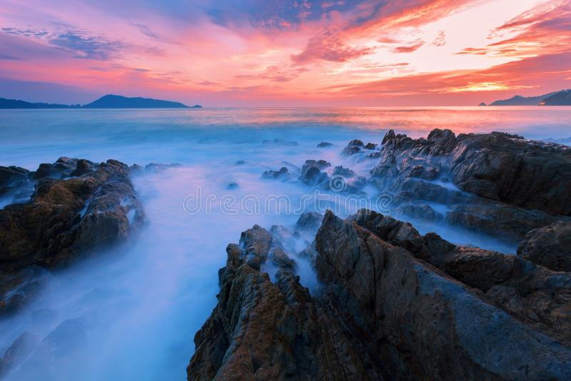 Długi ujawnienie wizerunek Dramatyczny nieba i fala seascape z skałą fotografia stock