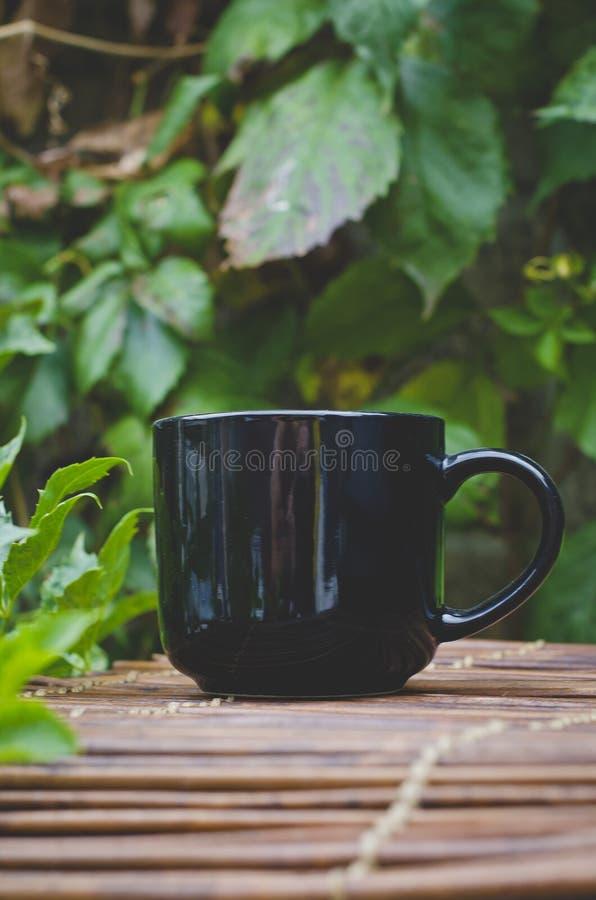 Długi widok pusty czarny kawowy kubek na bambusowej kawiarnia stołu krawędzi zdjęcia stock