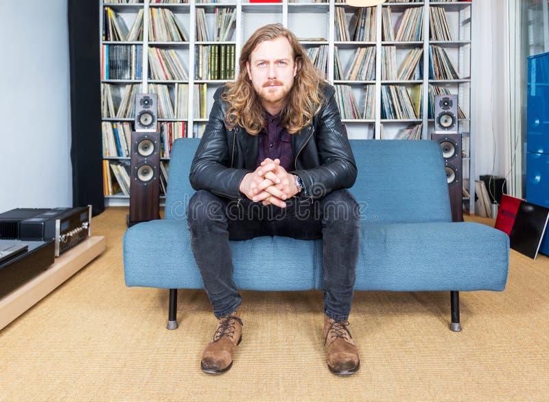 Długi z włosami mężczyzna intensively słucha muzyka obraz royalty free