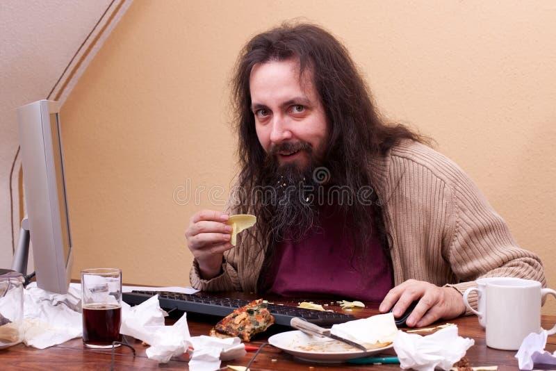 Długi z włosami nieuczesany mężczyzna obsiadanie przy komputerem obraz stock