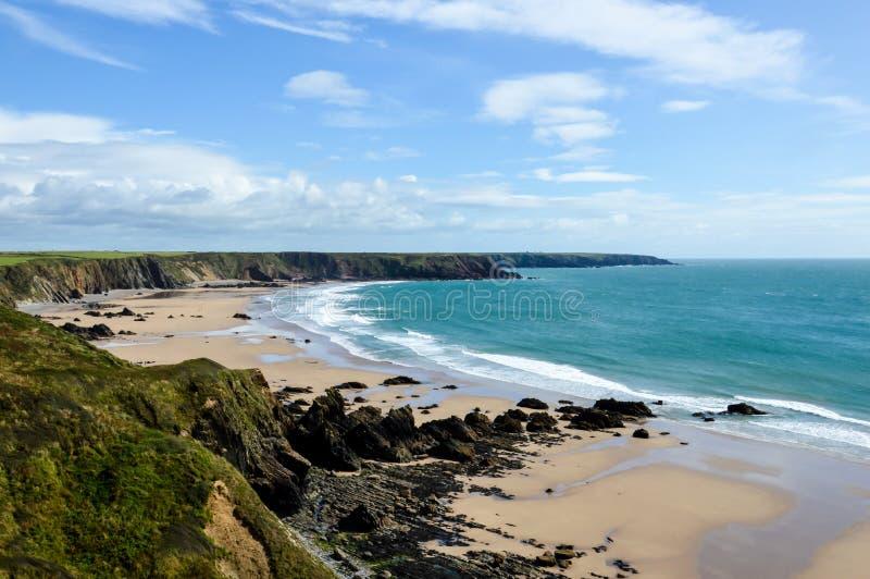 Długi zakres dzika niewygładzona linia brzegowa na słonecznym dniu i plaża w czasie odpływu morza Z falezami za Marloes piaski, P obrazy stock