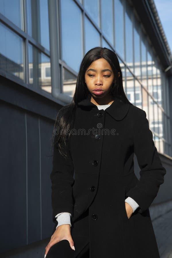 Długie włosy Afrykański kobieta portret w czarnym żakieta wezgłowiu budynek w miasta tle obrazy stock