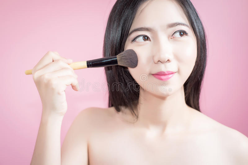 Długie włosy azjatykcia młoda piękna kobieta stosuje kosmetyka proszka muśnięcie na gładkiej twarzy odizolowywającej nad różowym  fotografia stock