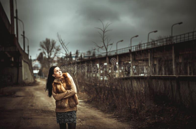 Długie włosy brunetki dziewczyna plenerowa z starym przemysłowym mostem behind zdjęcie stock