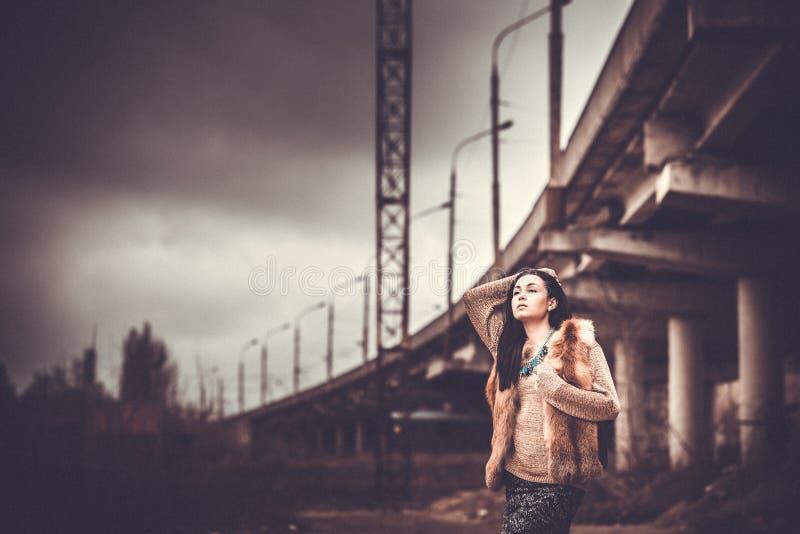 Długie włosy brunetki dziewczyna plenerowa z starym przemysłowym widokiem behind, zbożowy skutek obrazy royalty free