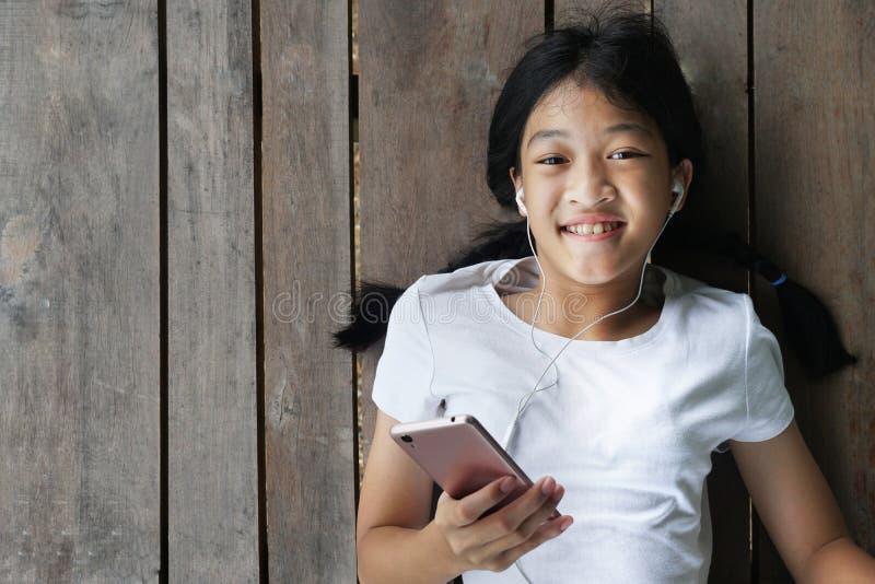 Długie włosy dzieciak dziewczyna z białą koszulką z mobilnym mądrze telefonem słucha muzyka białą słuchawką kłaść puszek dalej zdjęcie royalty free