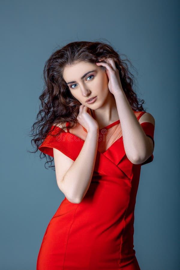 długie włosy Piękno Seksowna Śliczna dziewczyna jest ubranym w mody czerwieni smokingowy pozować na ble szarość tle zdjęcie stock