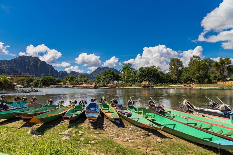 Długiego ogonu łodzie na zmierzchu przy Pieśniową rzeką, Vang Vieng, Laos obraz royalty free