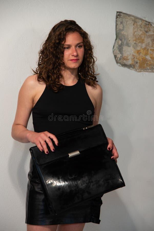 Długość portret młoda kędzierzawa brunetki kobieta z czarną teczką w jej ręce fotografia royalty free