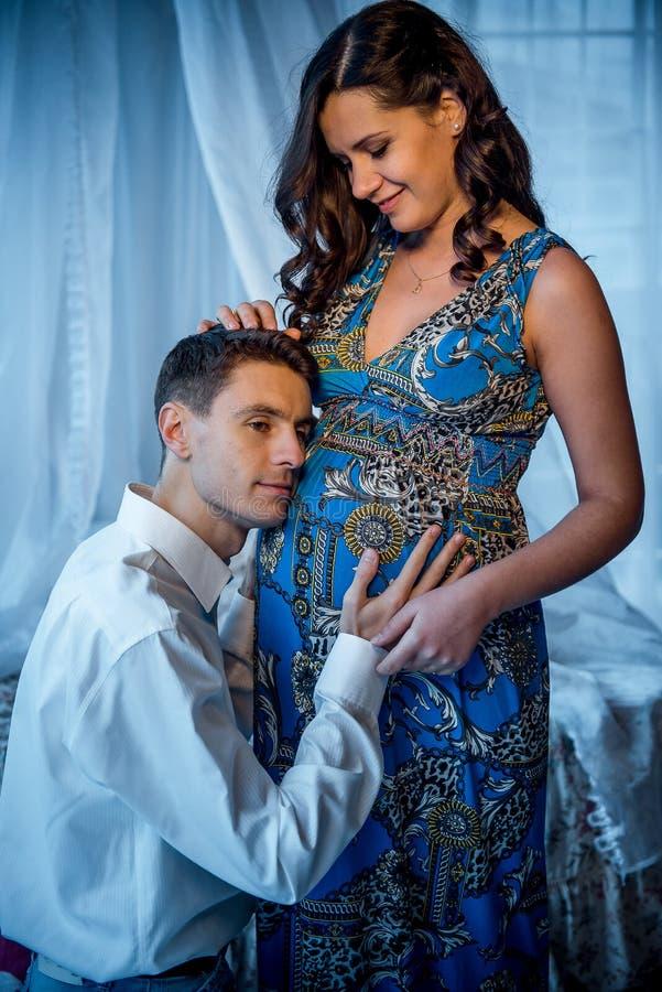 Długość portret przystojny męża słuchanie żołądek jego piękna powabna ciężarna żona i macanie obraz royalty free