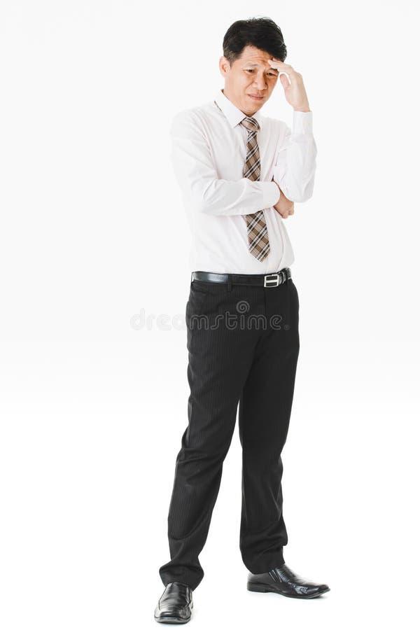 Długość portret w średnim wieku, przystojny, Azjatycki, biznesmen, w białej koszula, paskował krawat cierpi od ostrej migreny, gr zdjęcie stock
