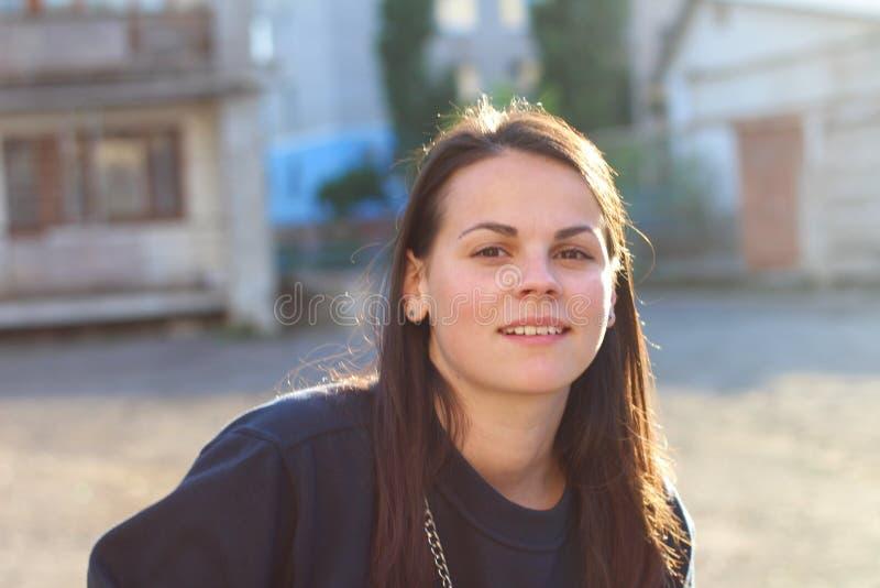 długowłosa brunetki dziewczyna opiera nad pram na tle sklepowi okno Portret Europejska kobieta w błękitnej bluzie sportowej fotografia royalty free