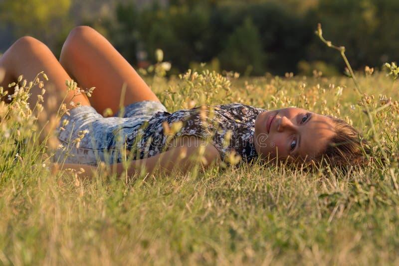 Długowłosa dziewczyna siedzi w trawie obraz royalty free