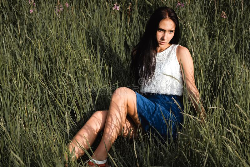 Długowłosa nastoletnia dziewczyna siedzi na trawy łące obrazy royalty free