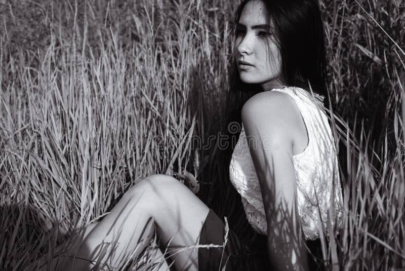 Długowłosa nastoletnia dziewczyna siedzi na trawy łące zdjęcie stock