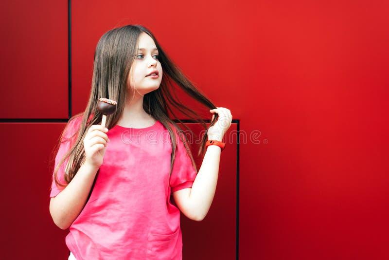 Długowłosa nastoletnia dziewczyna z czekolady chupa chups zdjęcie royalty free