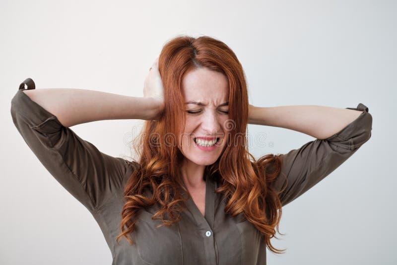 Długowłosa piękna młoda brunetki kobieta zakrywa jej ucho z jej rękami fotografia stock